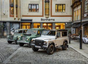 Der zweimillionste Landrover Defender - flankiert von seinen älteren Brüdern - verdiente während der Bonhams-Auktion 550.000. Der Erlös geht an zwei Wohltätigkeitsorganisationen. Bild: Jaguar Land Rover