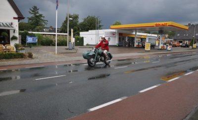 Cadzand in de regen Ernie is ooit, als dertienjarige naar Cadzand Bad gefietst. We besluiten de rit op de motor over te doen. In dertig jaar is Nederland erg veranderd. En vier ouwe motorfietsen zijn wat anders dan een fiets. Zeker als er een zijspan mee rijdt. De rit volgt zo natuurgetrouw de authentieke route. We rijden over fietspaden, door inmiddels gegroeide woonwijken, plantsoenen en winkelcentra. Het is hartje zomer dus iedereen denkt dat we een lokale vakantieactiviteit zijn. Het veer Kruiningen-Perkpolder is niet meer. Maar zo'n tunnel heeft ook wel wat. De oudgedienden daveren door de kilometerslange pijp die zich van voor tot achter met geblaf, geknal en gegrom vult. Wat spelen met de voorontsteking levert een onweersbui van daverende knallen en blauw paarse uitlaatvlammen op. Vakantiegangers het caravans dwarrelen verdoofd in ons spoor. De geluidsorkaan loopt ook voor ons uit. Dat heeft blijkbaar iets te maken met resonantiefrequenties. Het oplopen van blijvende gehoorschade is een feest! Aan de andere kant van de tunnel komen we in een wat sombere klimaatzone, maar we halen Cadzand Bad, de badplaats met de lelijkste boulevard ooit. Het is een lange dag geweest en er moet dus eerst gefoerageerd worden. We lopen naar de Zeemeeuw. Daar is het gezellig druk op het terras. Iedereen knipoogt tevreden naar de zee. De bewolking neemt toe. Jacks en helmen mogen in een hoek van het terras uitrusten. We doen een bier en regelen asbakken. Er zit een man met Harley tattoos op zijn anabole schouders. Hij heeft een aanzienlijk jongere dame bij zich en is erg druk met het negeren van motorrijders zonder Harley tattoos. Zou dat eigenlijk pijn doen, een tattoo zetten? Er vallen wat druppels. Wij bestellen nog wat bier en een driedubbele bittergarnituur. Gefrituurde dingen zijn goed. Want een motor kan ook niet zonder olie. Het begint serieus te regenen. Het terrasvolk vlucht massaal naar binnen. Zomerregen is niet erg. We doen gewoon onze motorspullen weer aan. En waarom